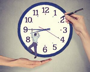 Business man trying to stop time. Man hanging on clock arrow isolated on gray office wall background. Time pressure passing past concept