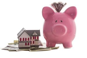 Close up of a pink piggy bank with dollars beside miniature house model on white background-1